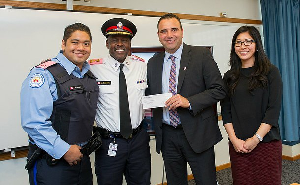 two men in uniform with a  man a woman holding a cheque