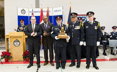 A man holding a trophy surrounded by 5 other men, some in uniform and some in suits.