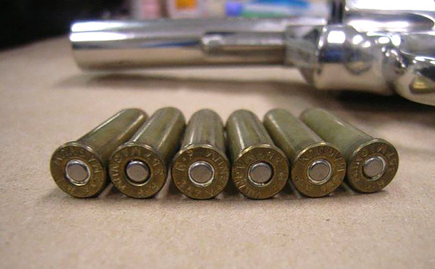 Bottom of bullets with handgun in background