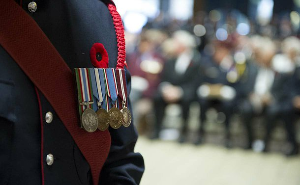 Medals on a uniform in the left foreground of the photo in focus while the right side, an audience of people, is out of focus
