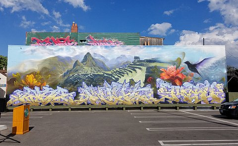 A mural on a building beside a parking lot
