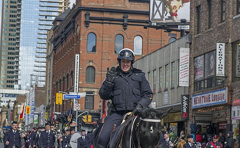 A woman in TPS uniform on a horse on a street