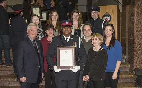A man in TPS uniform holding a framed certificate surrounded by a group of people