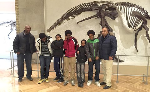 Two men and four boys stand together near fossils on the wall