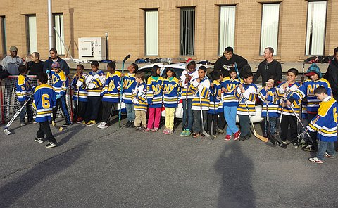 A group of girls and boys in hockey uniform stand in a line with adults in a parking lot