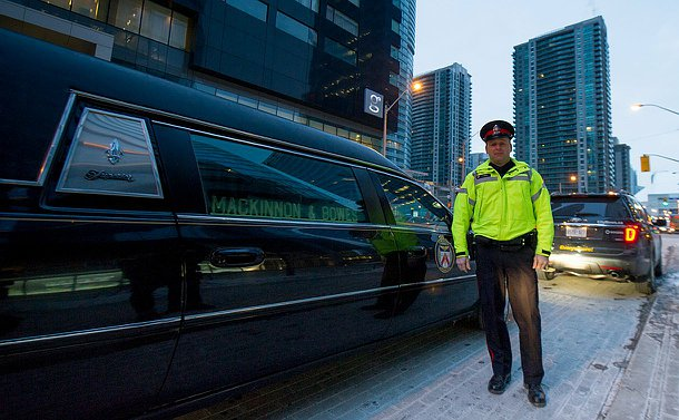 A man in TPS uniform stands beside a hearse with a TPS logo on the passenger door