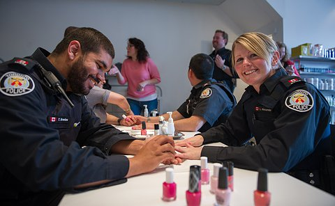 A male officer is putting on nail polish on a female officer.