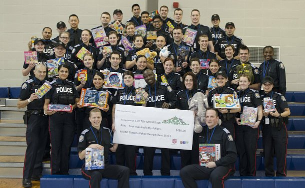 A group of men and women in TPS uniform on bleachers holding toys and an oversized cheque