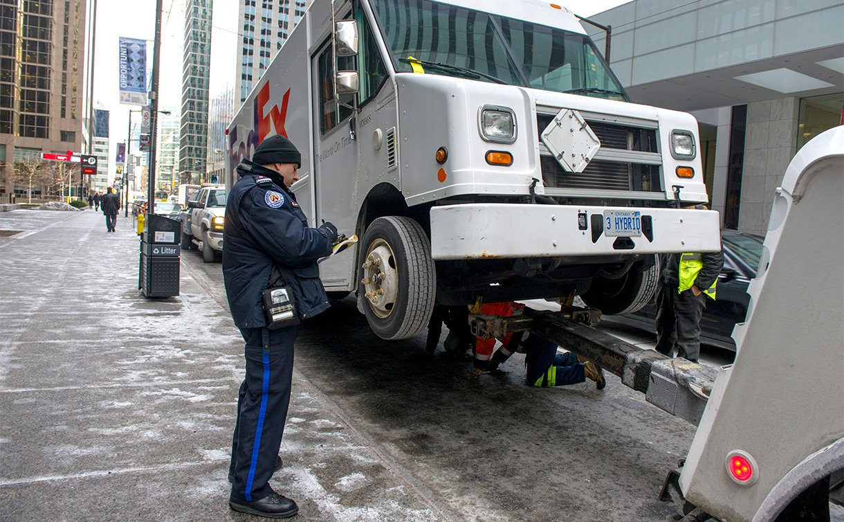 A man in a  TPS parking uniform writes a ticket on a pad near a truck being lifted by a tow truck