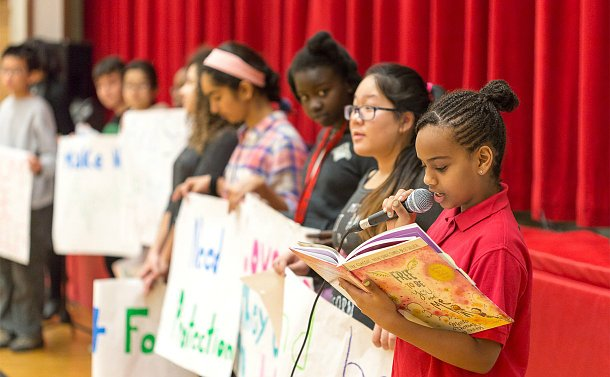 A girl holds a microphone and looks at a book as other students look on