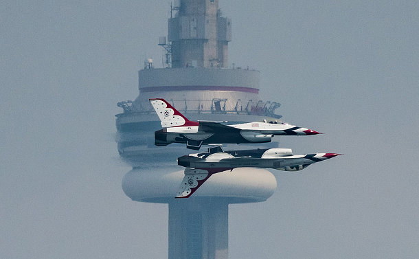 Two planes, one upside down flying together with CN Tower in background