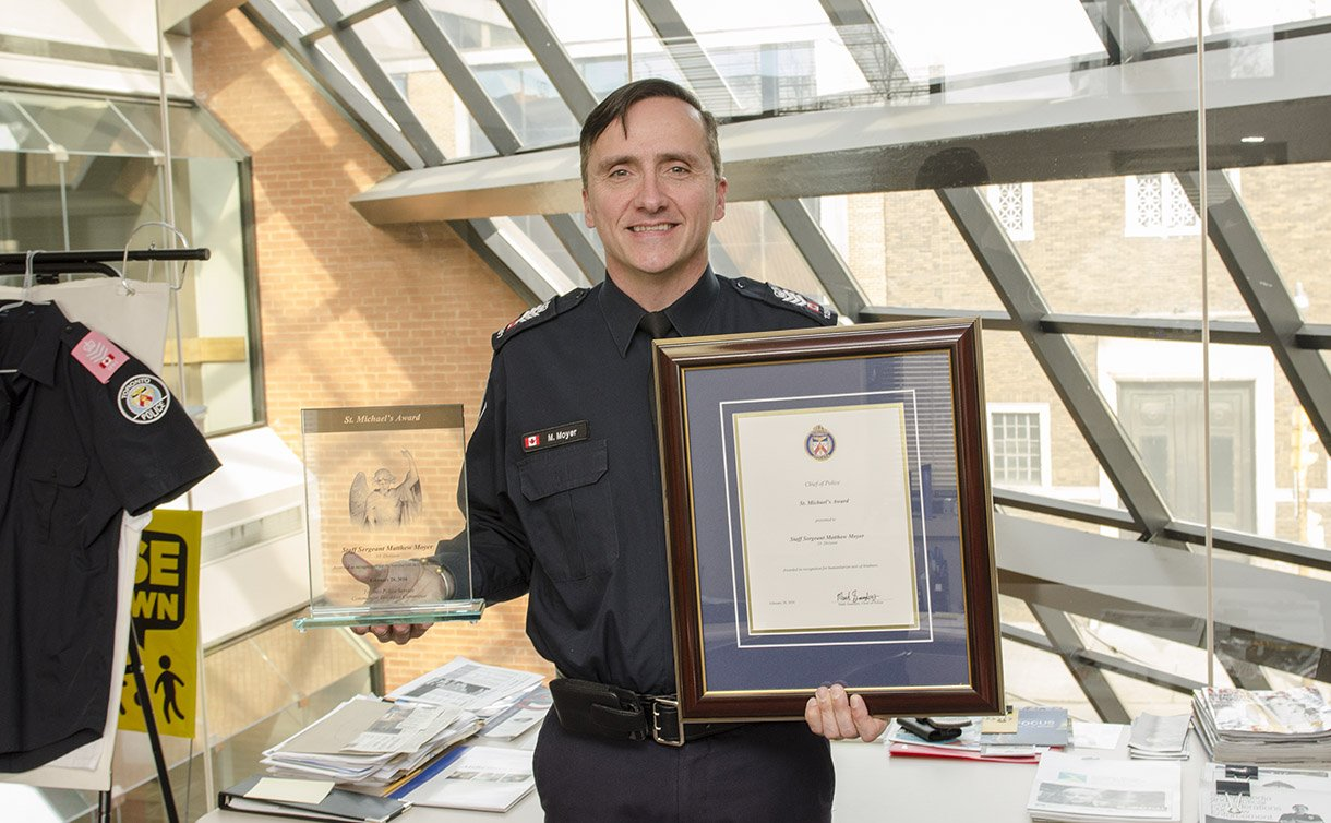 A man holding a framed certificate and award