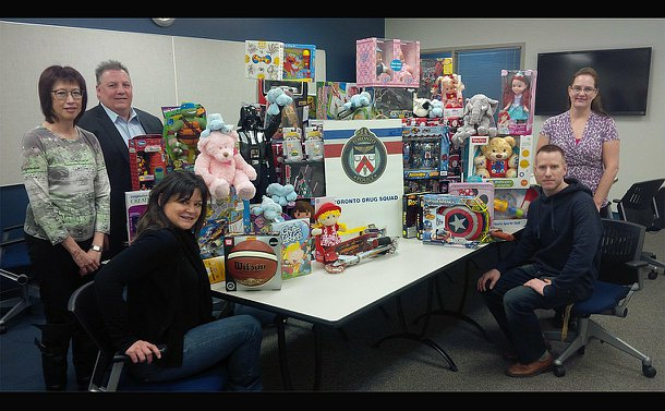 People standing and sitting on either side of a large table with a pile of presents on top