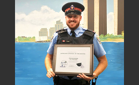 Man in a uniform holding an award plaque with his name on it as an auxiliary officer of the month