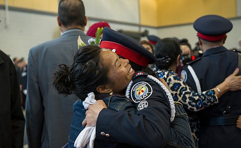 A woman hugging her sister who is wearing a TPS uniform