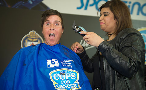 A woman in a barber's smock is shaved by another woman with electric shears