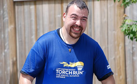 A man smiles as he holds forward a wet t-shirt