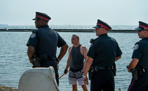 Three men in TPS uniform look to left as a man in a tank top looks forward by the water