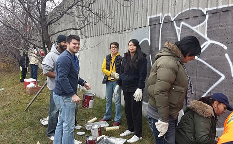 People standing beside a large concrete wall with graffiti on it and with paint supplies