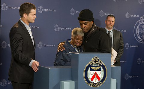 A woman crying as a man holds her around the shoulders comforting her, both standing at a toronot police podium with a detective to their right.