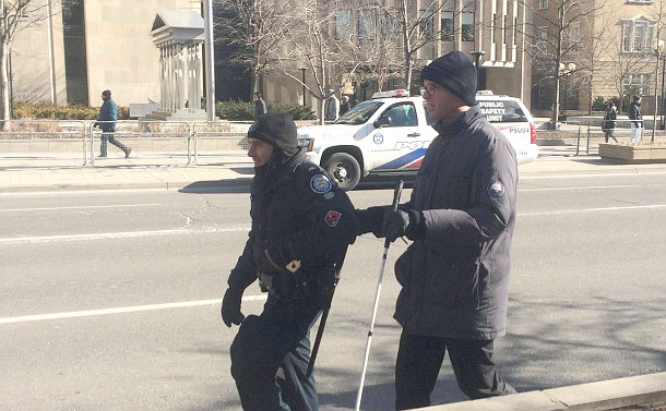 A man with a white cane holding the arm of TPS officer on a street