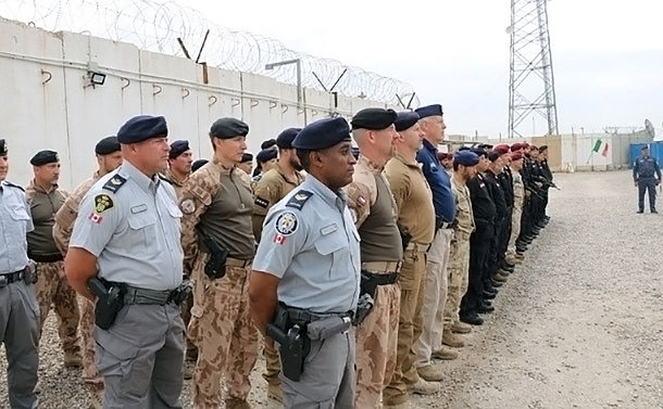 Large group of uniformed men surrounded by concrete walls stand on parade