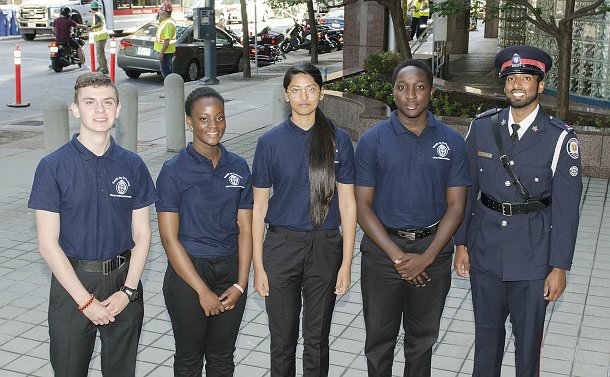A man in TPS uniform with four teens in matching golf shirts