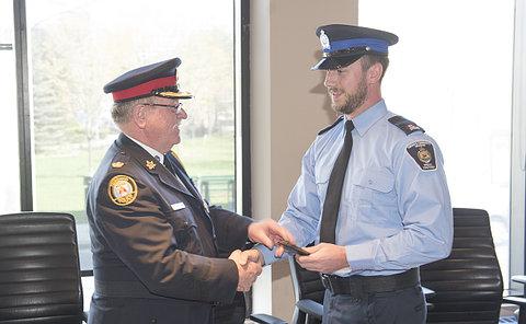 A man in TPS uniform hands a wallet to a man in TCH uniform