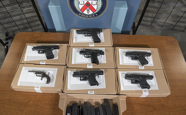 A table with six black handguns and one silver revolver