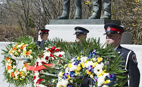 Three police officers stand behind wreaths near a large statute and granite wall