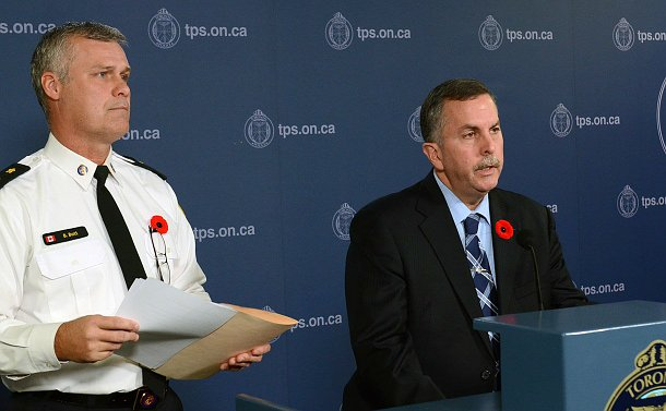 Two man, one in a police uniform and the other in a suit, in-front of a conference podium