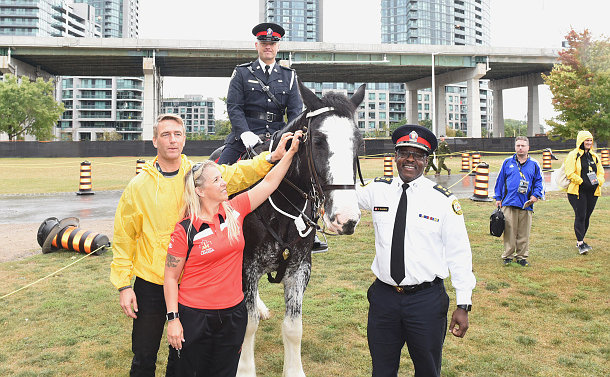 Three men, two of them wearing police uniforms, and a woman stand next to a horse in a park like environment