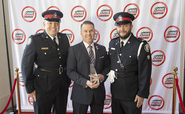 Two men in police uniform with another man holding an award