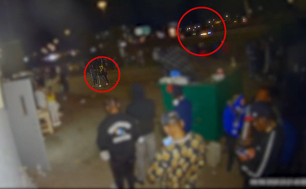 Camera view of a back of a building with a large group of men and women gathered together at night time. A highway with passing cars is visible near by. Two circles identify the group of wanted suspects and a vehicle on the highway.