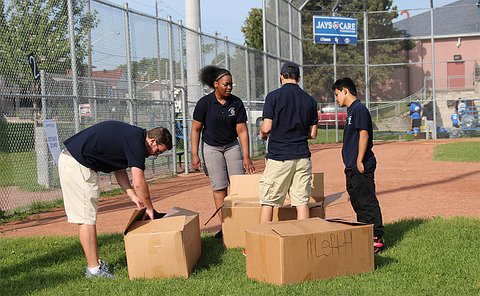 Boys and girls in YIPI uniforms opening boxes on a baseball field