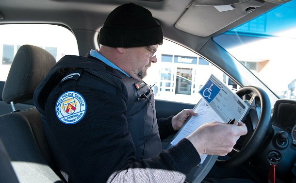 A man in parking uniform sitting in a car holding a permit while writing something down