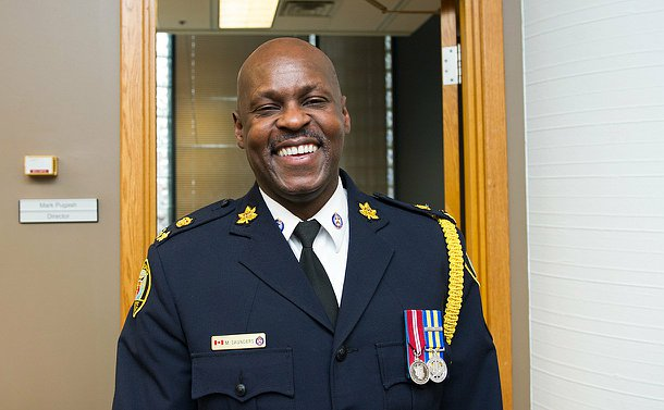 An officer in uniform smiling