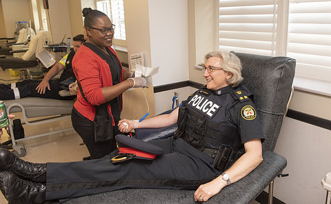 A woman in TPS uniform being prepped by a nurse to give blood