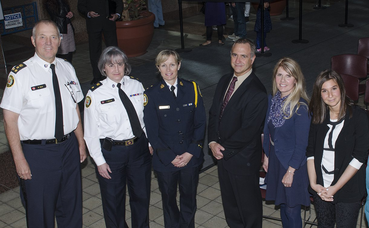 A man and two women in TPS uniform standing in a line with a man and two other women