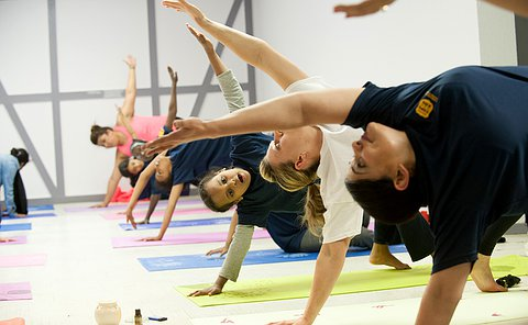 Two women in a yoga pose among a row of girls in similar poses as one girl looks on