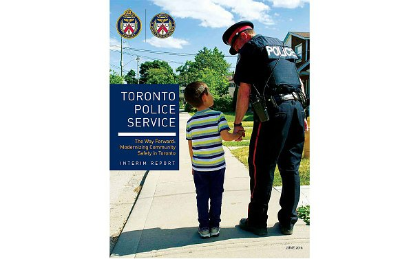 A report cover, photo of a TPS officer holding hands with a child