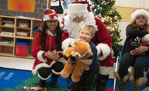 A child holding a teddy bear smiles while being embraced by a Santa as a woman looks on