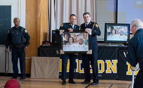 One officer giving a framed painting to another officer