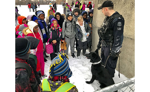 Officer talking to children with a dog.