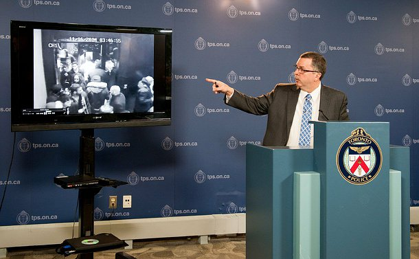 A man in a suit standing at a Toronto Police podium pointing to a television which shows video footage.