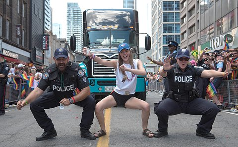 Two TPS officers and a woman dancing