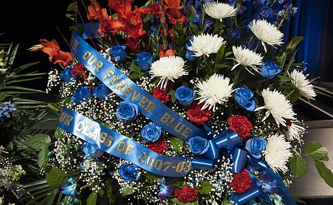 """Flowers with inscription """"Our forever Blue, Class of 2007-03"""" along a ribbon"""