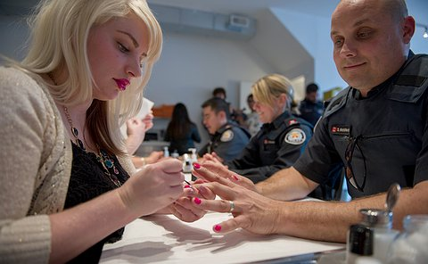 An officer in uniform looks on as a manicurist paints his nails.
