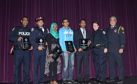 A group of people standing in a row, some hold awards, three are men in TPS uniform, one is a woman in TPS uniform