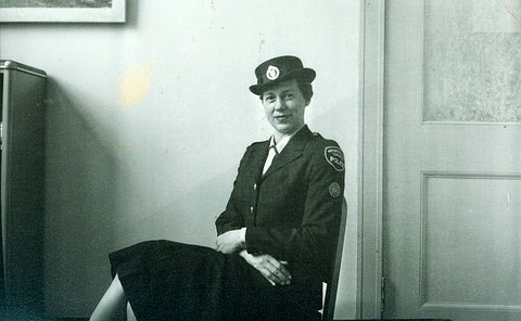 An old black and white photo of a woman sitting in an office in an old police woman uniform,